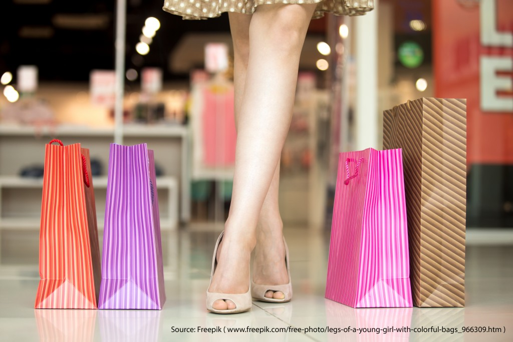 Close-up of woman crossed beautiful legs standing in shopping centre in front of clothing store with colorful shopping bags around on floor. Fashion, sale, shopping time concept